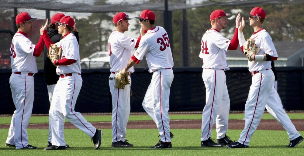 Ball State's baseball team congratulates each other after winning the first game of a double-header against Dayton on March 18. DN PHOTO GRACE RAMEY
