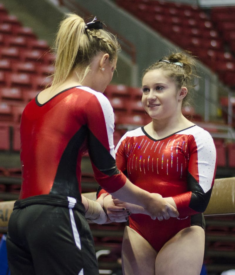 Junior Sarah Ebeyer talks to freshman Kaitlyn Menzione before Menzione perfumed on the beam during the meet against Townson on Jan. 17 at Worthen Arena. DN PHOTO BREANNA DAUGHERTY