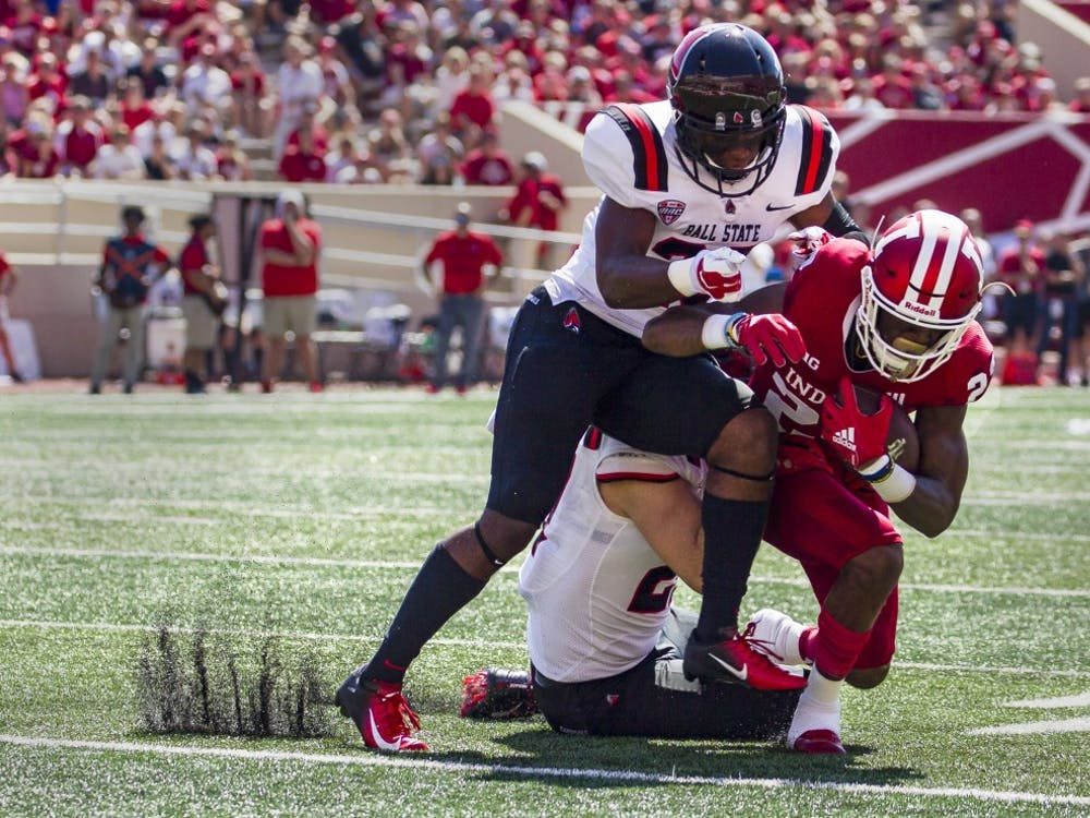 Sophomore wide receiver Whop Philter is tackled by junior safety Brett Anderson II and offensive line backer Jimmy Daw, Saturday, September 15, at Memorial Stadium, in Bloomington, IN. Ball State lost to IU, 10-38, making this their second loss of the season. Grace Hollars,DN