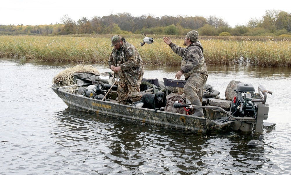 Casey Sunsdahl, right, of Soudan tosses a decoy to the front of his duck boat after a morning of hunting on Lake of the Woods. His hunting partner is Brad Redmond of Virginia. (Sam Cook/Duluth News Tribune/TNS)