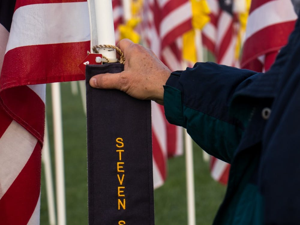 At Minnetrista's Flags of Honor Dave McGalliard stops to look at a flag Tuesday, Sept. 11, 2018, in honor of a former student of his and a firefighter who passed away. Black ribbons on Flags represent lives that have been lost in the line of duty. Eric Pritchett, DN