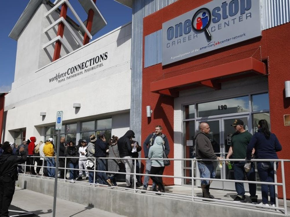 In this March 17, 2020, file photo, people wait in line for help with unemployment benefits at the One-Stop Career Center in Las Vegas. A record-high number of people applied for unemployment benefits last week as layoffs engulfed the United States in the face of a near-total economic shutdown caused by the coronavirus. The surge in weekly applications for benefits far exceeded the previous record set in 1982. (AP Photo/John Locher, File)