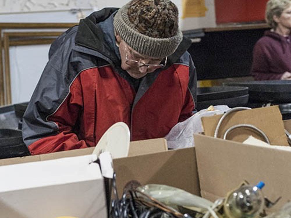 A community member sorts through a box of machine parts during the auction in downtown Muncie on Feb. 16. The auction had a collection of items provided by Ball State, including furniture and electronics. DN PHOTO JONATHAN MIKSANEK