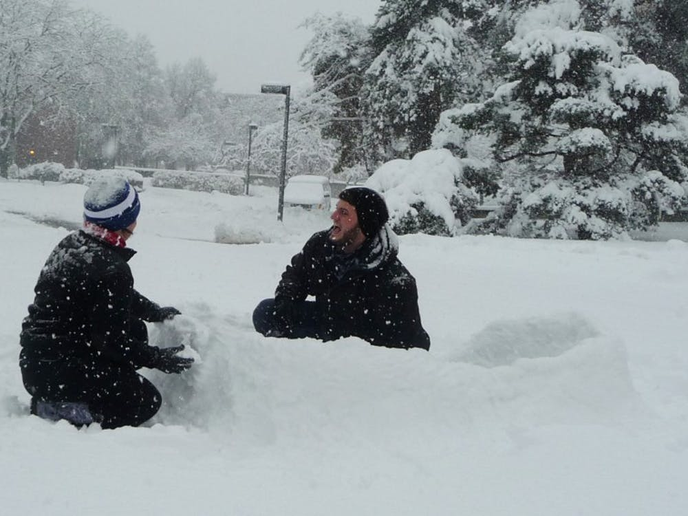 Gabe Weaver, a sophomore visual communications major and Katie Clark, a sophomore hospitality and food management major, crouch in the snow near Bracken Library. The two built the fort a few hours before the winter storm intensified. DN PHOTO SAM HOYT