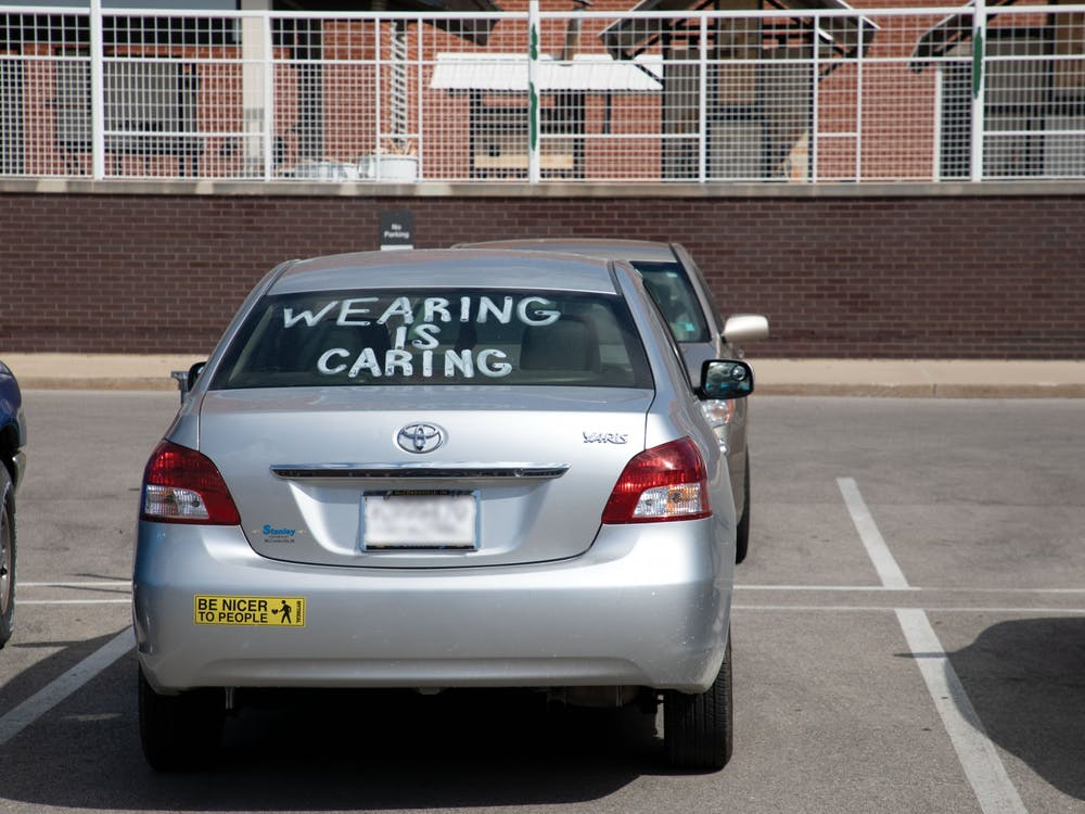 """A car sits parked with """"Wearing Is Caring"""" painted in the window Aug. 29 near the Arts and Journalism building. On AUg. 28, Ball State President Geoffrey Mearns sent out an email to students about COVID-19 cases at Ball State.Charles Melton, DN"""