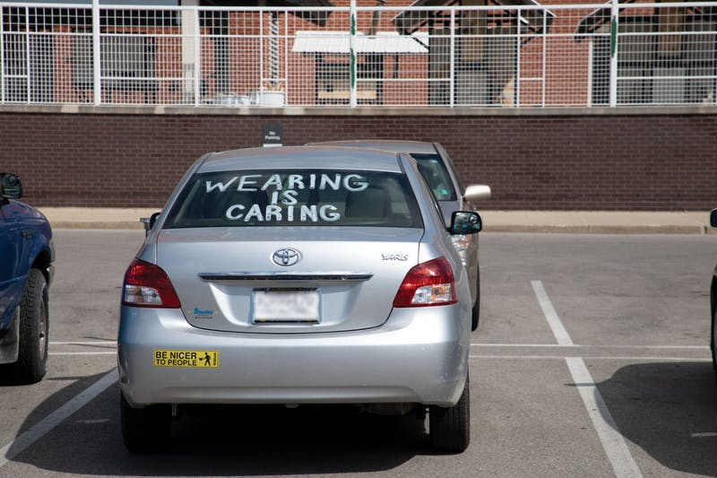 "A car sits parked with ""Wearing Is Caring"" painted in the window Aug. 29 near the Arts and Journalism building. On AUg. 28, Ball State President Geoffrey Mearns sent out an email to students about COVID-19 cases at Ball State. Charles Melton, DN"