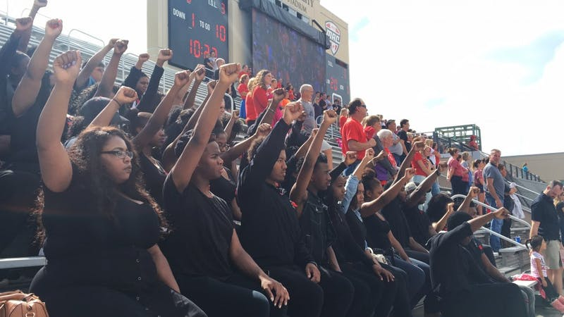 Students sit, raise fists during national anthem