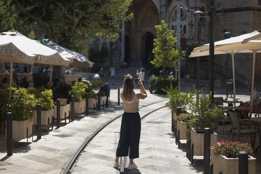 <p>A tourist take photos in town of Sóller, in the Balearic Island of Mallorca, Spain, Monday, July 27, 2020. Britain has put Spain back on its unsafe list and announced Saturday that travelers arriving in the U.K. from Spain must now quarantine for 14 days. (AP Photo/Joan Mateu)</p>