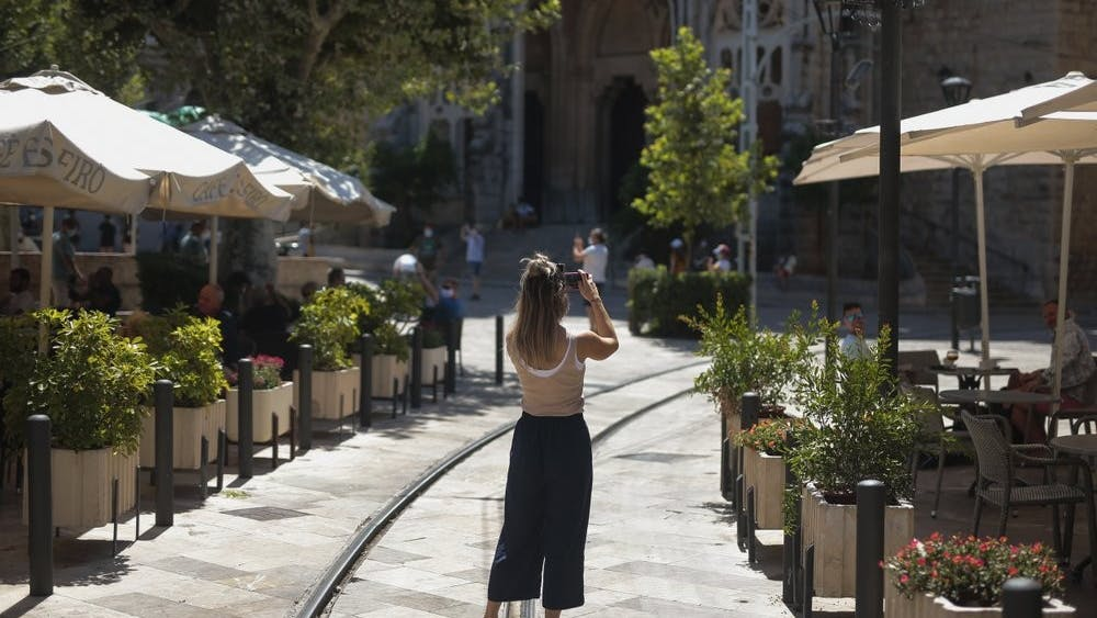 A tourist take photos in town of Sóller, in the Balearic Island of Mallorca, Spain, Monday, July 27, 2020. Britain has put Spain back on its unsafe list and announced Saturday that travelers arriving in the U.K. from Spain must now quarantine for 14 days. (AP Photo/Joan Mateu)
