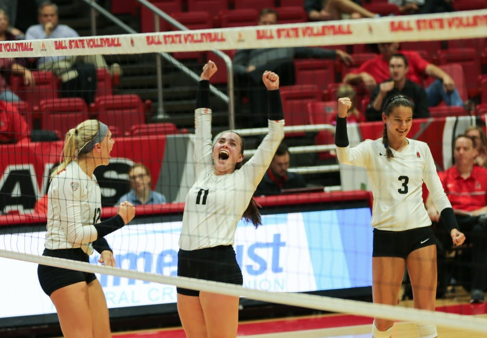 Sophomores Amber Seamen and Sydnee Vanbeek and junior Brooklyn Goodsel celebrate after getting a point against Toledo on Nov. 2 at John E. Worthen Arena. They won the game 3-1. Elliott DeRose, DN