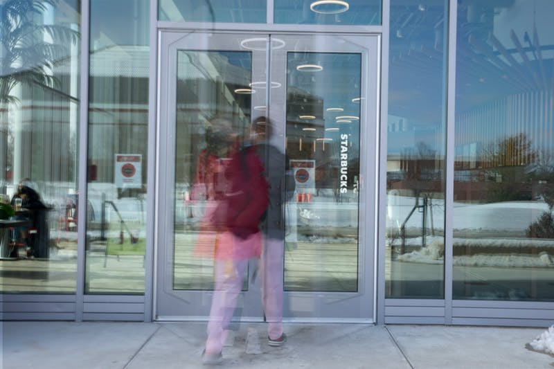 Students walk in and out of the doors at North Dining Hall Feb. 3, 2021. The new dining hall features multiple different new restaurants and an allergen free eatery. Jacob Musselman, DN Photo Illustration