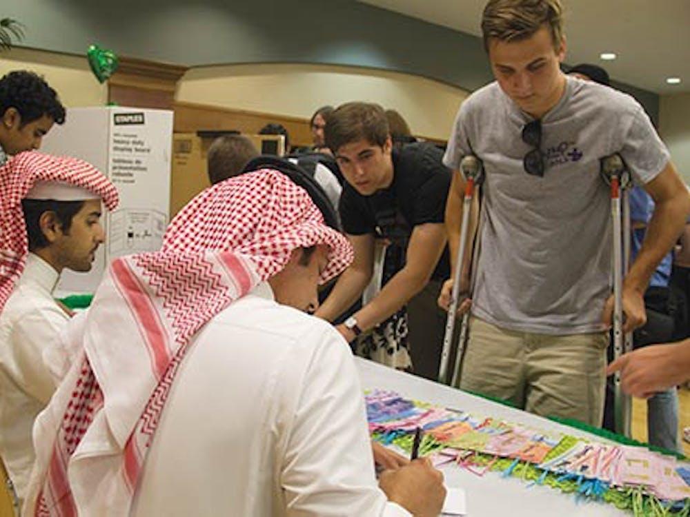 Nasser Alkhatani, a special education major, writes junior telecommunications major Nathan Wilson