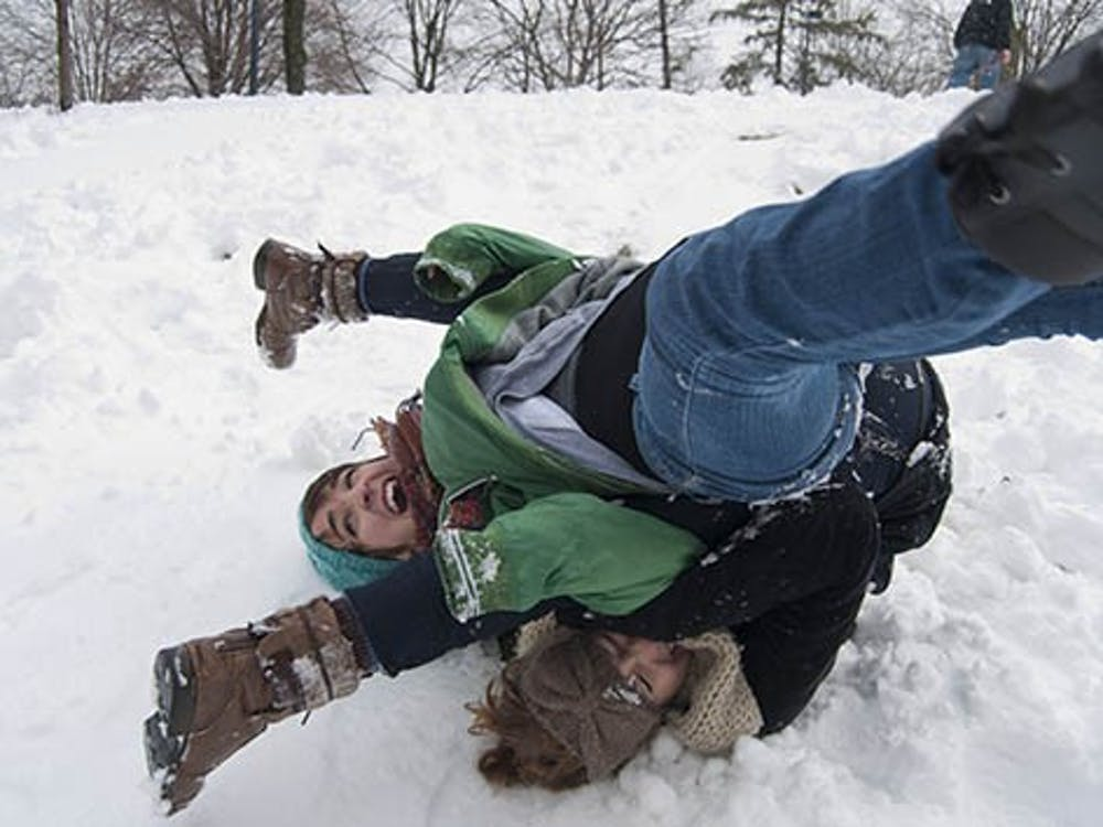 Stephanie Metzger tumbles over sophomore Kat Winton after falling off a makeshift sled.The snowstorm caused Ball State to close for two hours. DN PHOTO BOBBY ELLIS