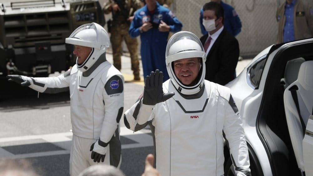 NASA astronauts Douglas Hurley, left, and Robert Behnken walk out of the Neil A. Armstrong Operations and Checkout Building on their way to Pad 39-A, at the Kennedy Space Center May 30, 2020, in Cape Canaveral, Fla. For the first time in nearly a decade, astronauts will blast into orbit aboard an American rocket from American soil, a first for a private company. (AP Photo/John Raoux)
