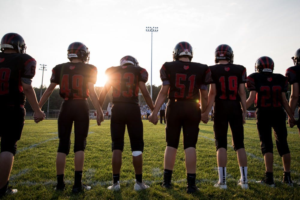 <p>Blackford Bruins players hold hands on the sideline during the coin toss Sept. 20, 2019, in Hartford City, Indiana. The Bruins finished the regular season at 5-4. <strong>Eric Pritchett, DN</strong></p>