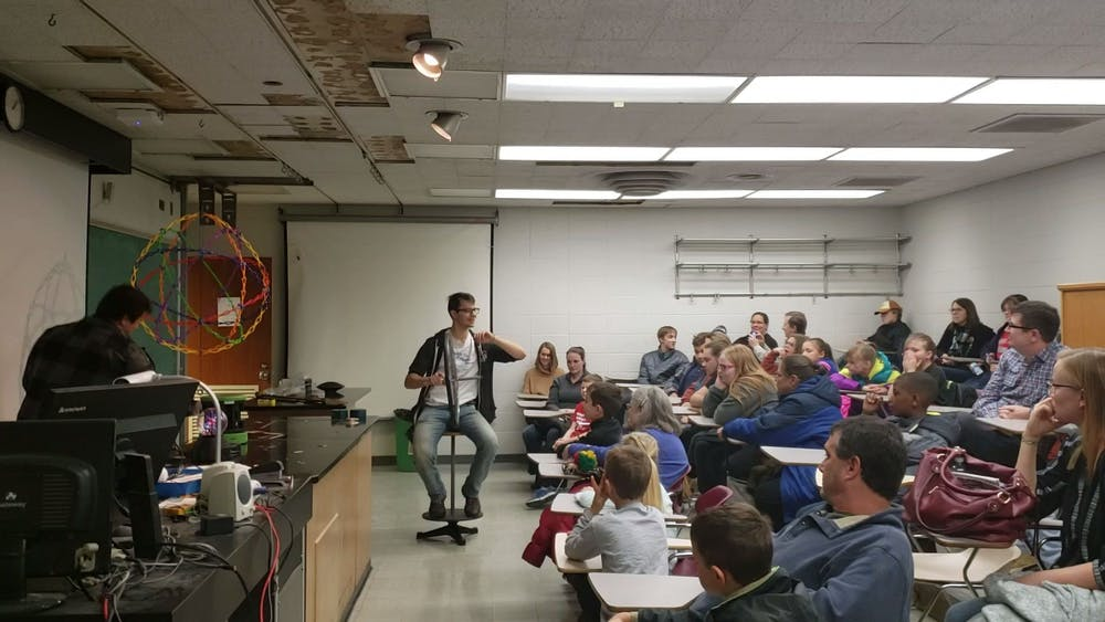 """A student from the Society of Physics Students (SPS) teaches attendees Nov. 9, 2019, about rotational motion using a bike wheel and a stool at the """"Clash of Sciences"""" event. SPS was one of three organizations at the event. Jaden Hasse, DN"""