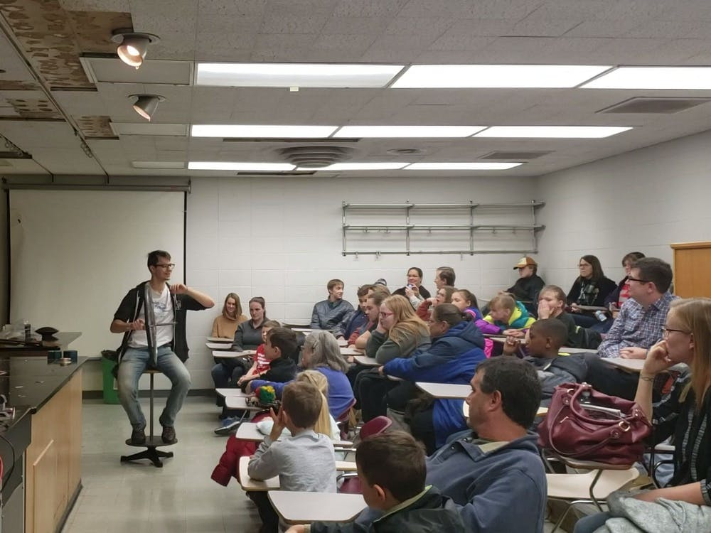 "A student from the Society of Physics Students (SPS) teaches attendees Nov. 9, 2019, about rotational motion using a bike wheel and a stool at the ""Clash of Sciences"" event. SPS was one of three organizations at the event. Jaden Hasse, DN"