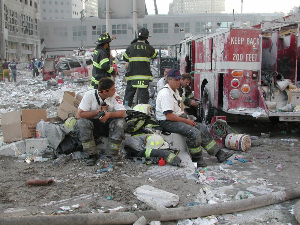 New York City firefighters sit in rubble from the collapsed towers of the World Trade Center Sept. 11, 2001. The New York City Fire Department was one of the first responders on scene when Flight 11 crashed into the north tower. U.S. Army Corps of Engineers, Photo Courtesy
