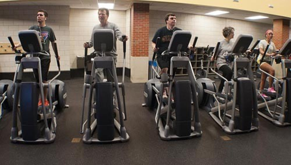 Patrons of the Student Recreation and Wellness Center work out on ellipticals Monday evening. The new year has brought more people attempting to get in better shape for New Year's resolutions. DN PHOTO BOBBY ELLIS