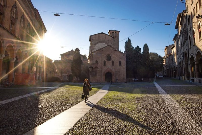 A woman walks past the Basilica of Santo Stefano, March 11, 2020, in Bologna, Italy. In Italy the government extended a coronavirus containment order previously limited to the country's north to the rest of the country beginning Tuesday, with soldiers and police enforcing bans. For most people, the new coronavirus causes only mild or moderate symptoms, such as fever and cough. For some, especially older adults and people with existing health problems, it can cause more severe illness, including pneumonia. (Massimo Paolone/LaPresse via AP)