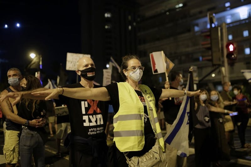 Protesters spread their arms to socially distance in the square outside of Prime Minister Benjamin Netanyahu's residence in Jerusalem, Saturday, Sept. 26, 2020, during a three-week nationwide lockdown in Israel to curb the spread of the coronavirus. (AP Photo/Maya Alleruzzo)