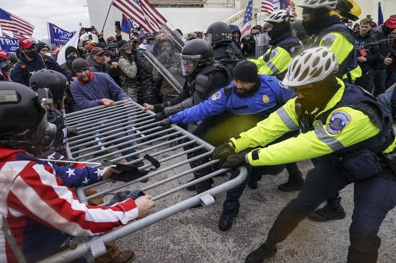 Trump supporters try to break through a police barrier and into the House Chamber, Wednesday, Jan. 6, 2021, at the Capitol in Washington. As Congress prepared to affirm President-elect Joe Biden's victory, thousands of people gathered to show their support for President Donald Trump and his claims of election fraud.(AP Photo/John Minchillo)