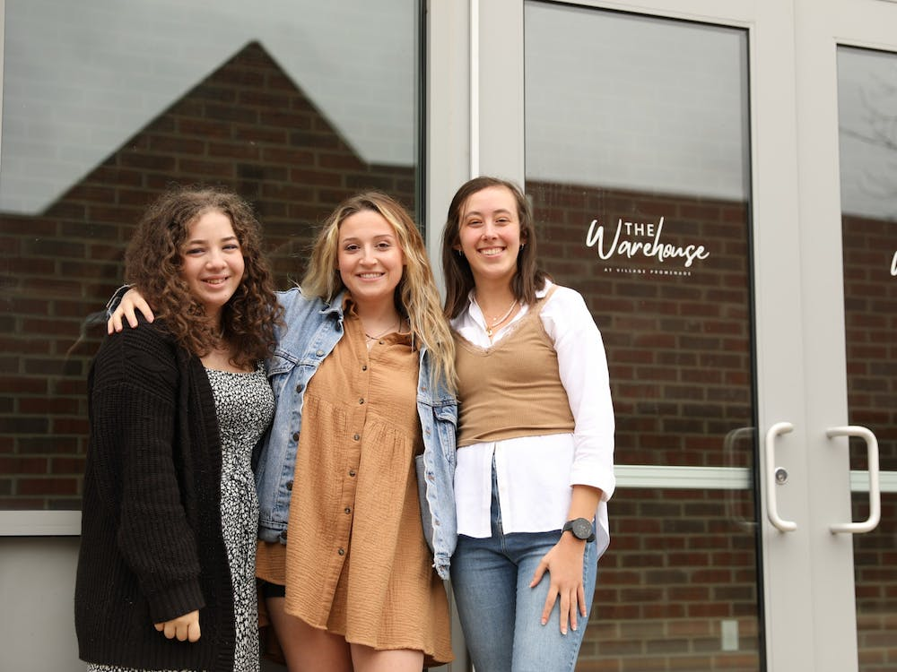 Jessica Wolfe (left), Brandi Osthimer (middle) and Maureen Kirk (right) pose in front of the location of the Fashion Merchandising Association's resale pop-up shop. The team started planning more than a month before the event. Rylan Capper, DN