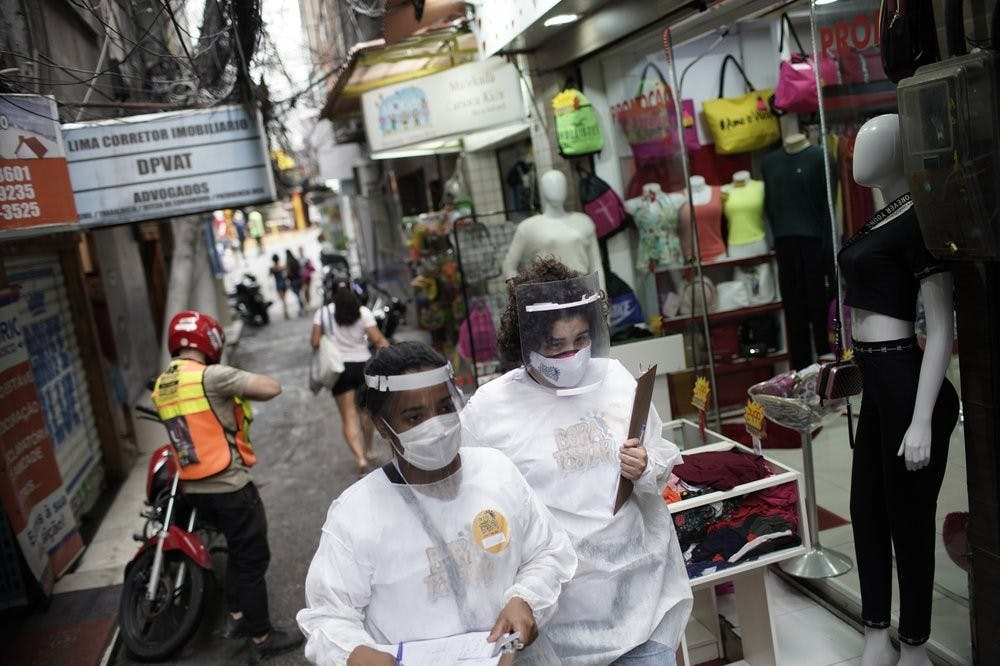 "Health workers walk through the Rocinha slum to test people for COVID-19 as part of a rapid test campaign by the civilian organization ""Bora Testar,"" or ""Let's Test"" in Rio de Janeiro, Brazil, Thursday, Oct. 8, 2020. Financed by crowdfunding and donations, the organization says it aims to test up to 300 people in the slum. (AP Photo/Silvia Izquierdo)"