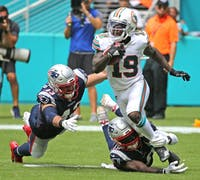 Miami Dolphins' Jakeem Grant (19) gets tackled by New England Patriots Nate Ebner (43) and Matthew Slater (18) in the fourth quarter on Sunday, Sept. 15 2019 at Hard Rock Stadium in Miami Gardens, Fla. (Charles Trainor Jr./Miami Herald/TNS)