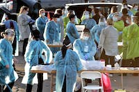 Medical personnel prepare to test hundreds of people lined up in vehicles June 27, 2020, in Phoenix's western neighborhood of Maryvale. PPE is running out again as the number of hospitalized patients climbs. (AP Photo/Matt York, File)
