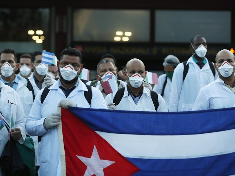 Medics and paramedics from Cuba pose upon arrival at the Malpensa airport March 22, 2020, in Milan, Italy. 53 doctors and paramedics from Cuba arrived in Milan to help with coronavirus treatment in Crema. (AP Photo/Antonio Calanni)