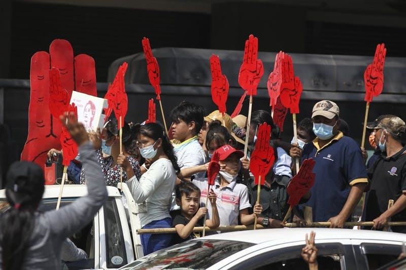 Protesters hold large three-fingered salute cutouts while onboard a vehicle in Yangon, Myanmar on Monday, Feb. 8, 2021. The salutes represent resistance to the military coup that happened last week. (AP Photo)