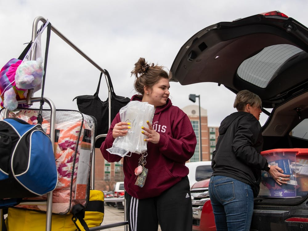 Senior exercise student Danielle Sprouse takes her stuff from the cart to her mom's car March 17, 2020, outside of Park Hall. Multiple students and their families were moving out of all the dorms. Jacob Musselman, DN