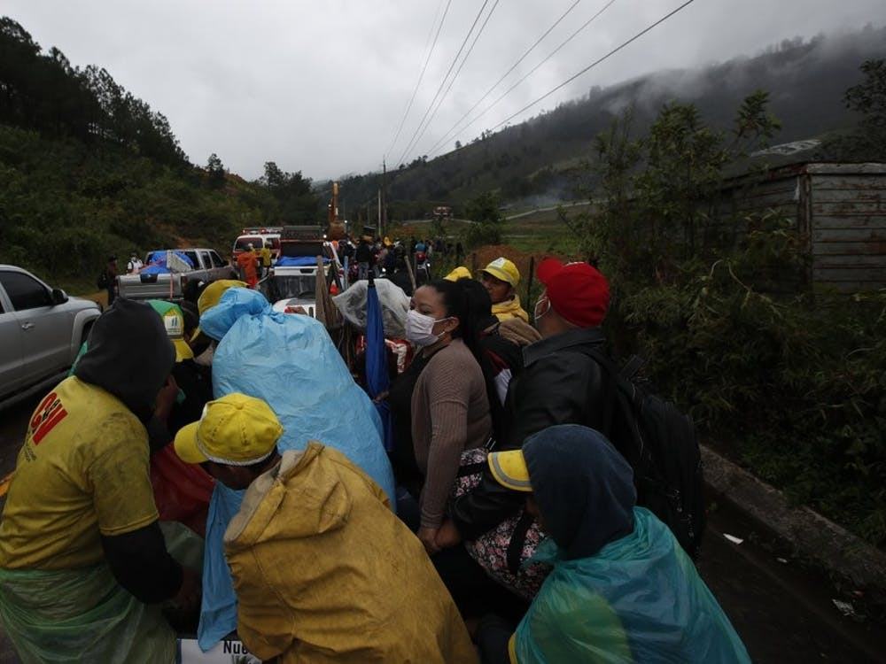 Residents traveling in the bed of a pickup truck wait on a road blocked by debris brought on by a landslide in the aftermath of Hurricane Eta, in Purulha, northern Guatemala Friday, Nov. 6, 2020. As the remnants of Eta moved back over Caribbean waters, governments in Central America worked to tally the displaced and dead, and recover bodies from landslides and flooding that claimed dozens of lives from Guatemala to Panama. (AP Photo/Moises Castillo)