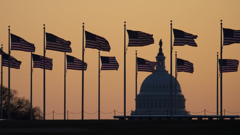 American flags blow in wind around the Washington Monument with the U.S. Capitol in the background at sunrise Jan. 20, 2020, in Washington. The impeachment trial of President Donald Trump will resume in the U.S. Senate on Jan. 21. (AP Photo/Jon Elswick)