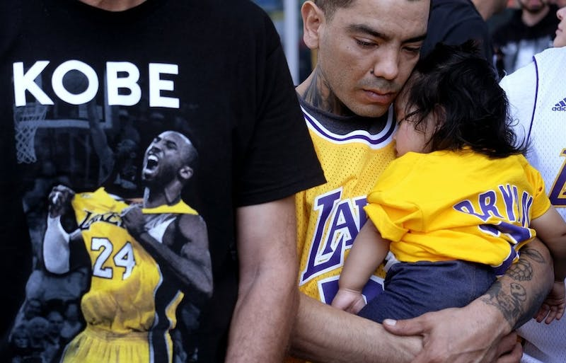 Erik Dominguez holds his 11-month-old daughter Isabella while watching the live stream of a public memorial for Kobe Bryant and his daughter, Gianna, Feb. 24, 2020, outside the Staples Center in Los Angeles. (AP Photo/Ringo H.W. Chiu)