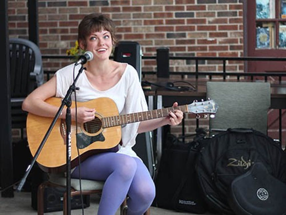 Marta Vitolins sings and plays guitar at the Cup during the free art show hosted by Glue & Scissors Marta is the Comunications Chief of Glue & Scissors, the Muncie-based group that strives to make people more aware of art. DN KRYSTAL BYERS