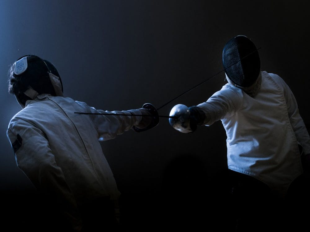 Sophomore computer science major Cole Ludwig, left, and sophomore criminal justice major Spencer Sabinske fence with sabres on Jan. 28 in the Student Recreation and Wellness Center during a fencing club meeting. DN PHOTO JONATHAN MIKSANEK