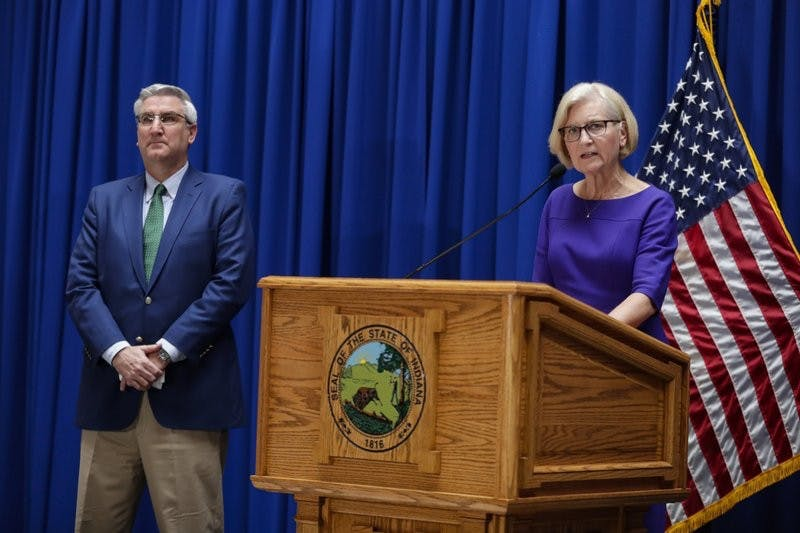 Dr. Kristina Box, Indiana Health Commissioner, answers questions about COVID-19 infections and its impact on the state as Indiana Gov. Eric Holcomb listens during a briefing at the Statehouse in Indianapolis, Tuesday, March 24, 2020. Holcomb ordered state residents to remain in their homes except when they are at work or for permitted activities, such as taking care of others, obtaining necessary supplies, and for health and safety. The order is in effect from March 25 to April 7. (AP Photo/Michael Conroy)