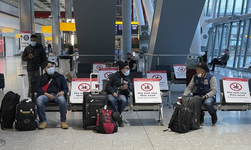 Travellers wait for their COVID-19 test results at Heathrow Airport in London, Sunday, Jan. 17, 2021. The UK will close all travel corridors from Monday morning to protect against the coronavirus, with all travellers required to have a negative COVID-19 test to enter the country. (AP Photo/Frank Augstein)