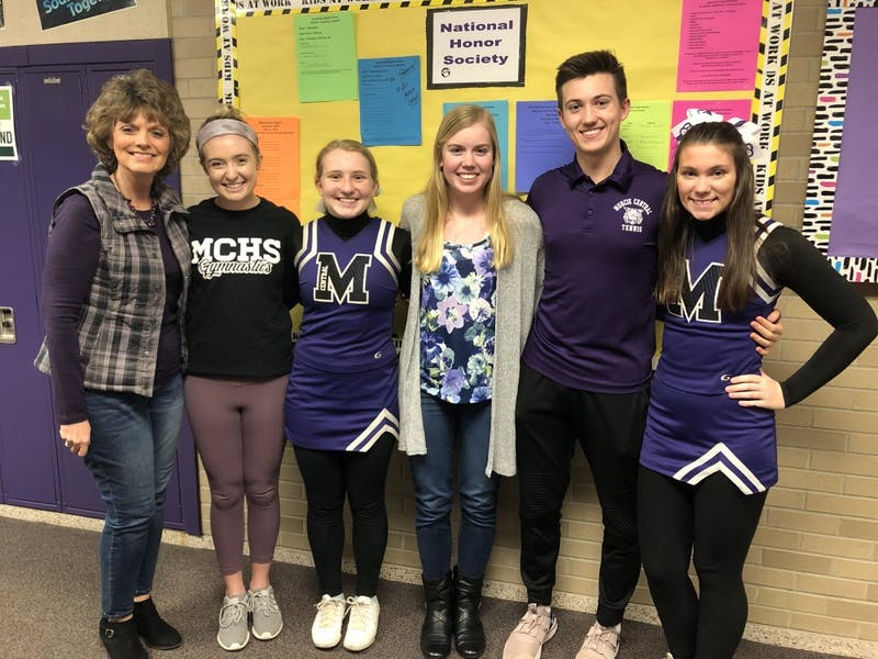 Lisa Letsinger, adviser of Muncie Central High School's chapter of National Honor Society (NHS), stands with Tara Horst, NHS president; Madeline Evans, NHS secretary; Allison Polk, NHS Treasurer; Erich Ong, NHS service hours coordinator; and Megan Clifford, NHS event coordinator, in front of a bulletin board where students can sign up for volunteer opportunities. Kayla Jackson, DN