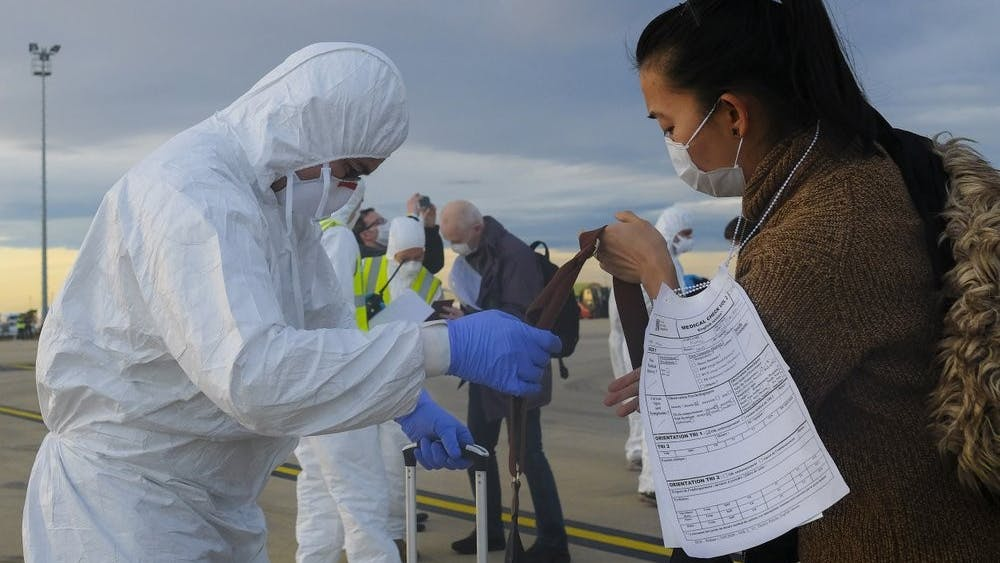 In this Feb. 2, 2020, photo, a worker wearing a protective suit checks the luggage of an evacuee from Wuhan, China, after their evacuation flight landed at an airport in Marseilles, France. China sent medical workers and equipment Monday to its just-completed, 1,000-bed hospital for treating victims of a new virus that has caused 362 deaths and more than 17,300 infections at home and abroad. (AP Photo/Arek Rataj)