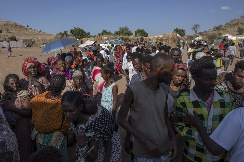 Tigranyan men and women who fled the conflict in Ethiopia's Tigray region, wait in line to receive aid, at Umm Rakouba refugee camp in Qadarif, eastern Sudan, Saturday, Dec. 5, 2020. (AP Photo/Nariman El-Mofty)