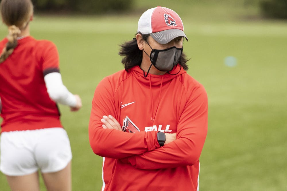 Cardinals head coach Josh Rife stands with the team during pregame practice March 26, 2021, at Briner Sports Complex. The Cardinals won 2-1 in overtime. Jacob Musselman, DN