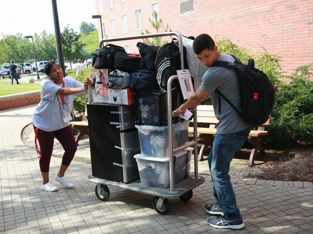 Students guide a trolley to the entrance of Brayton/Clevenger hall August 14, 2019, outside LaFollette Complex. Students under the premium plan were the first to move in to their residence halls. Rohith Rao, DN