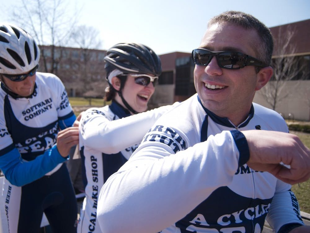 Andy Payne, a cycling team member, has his number pinned on by Rebecca Zink while Connor O