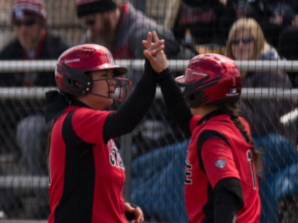 Madison Lee high fives Madd Labrador after Lee scored a run in the second inning. Ball State lost to Kent State April 7 at the Softball Field at First Merchants Ballpark Complex. Eric Pritchett, DN