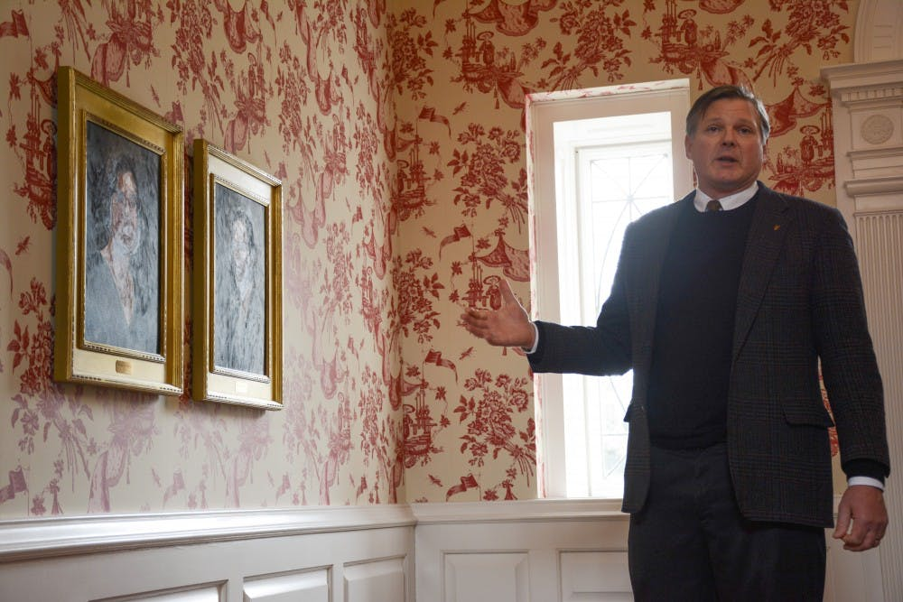 <p>Board of Trustee member Thomas Bracken gestures to portraits of his family members in the Bracken House on March 15 during the house tour. Bracken is now suing the city of Muncie and other municipal agencies for funding for the Madjax project downtown.</p>