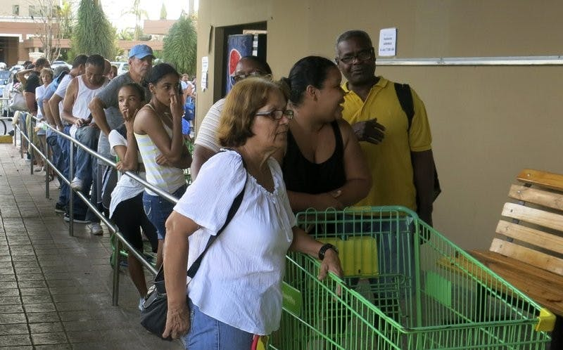 People wait in line outside a grocery store to buy food that wouldn't spoil and that they could prepare without electricity, in San Juan, Monday, Sept. 25, 2017. Most stores and restaurants remained closed Monday. Nearly all of Puerto Rico was without power or water five days after Hurricane Maria. AP Photo