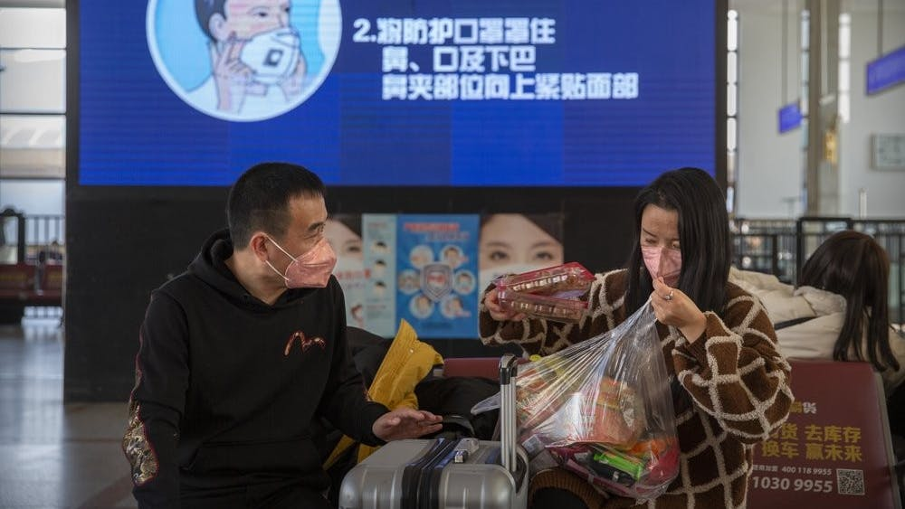 Travelers wear face masks as a screen shows a video about the proper way to wear a mask at the Beijing Railway Station in Beijing, Friday, Jan. 31, 2020. The U.S. advised against all travel to China on Friday after the World Health Organization declared the outbreak of a new virus that has spread to more than a dozen countries a global emergency. (AP Photo/Mark Schiefelbein)
